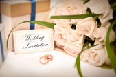 esküvői meghívó, gyűrűk, ajándékok és rózsák