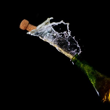 :Bottle of Champagne with popping cork and Champagne spray