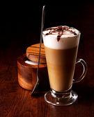 hrnek latte na dřevěný stůl s lžící a cukru