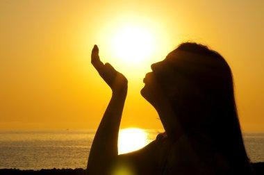 Woman silhouette kiss sun