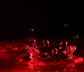 stříkající vodě v červené barvě s kapkami
