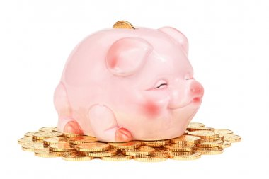 Pink piggy bank on pile of coins.
