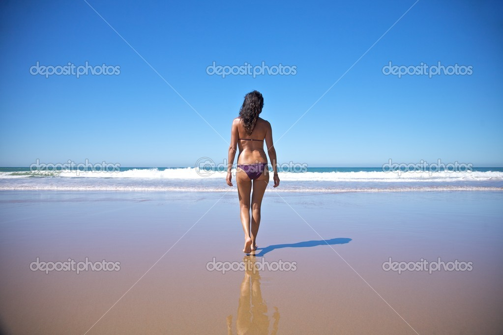 Woman walking towards water at seashore