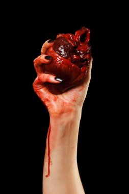 Human heart in hand isolated on black