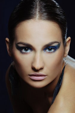 Young beautiful woman with blue make-up in long earrings