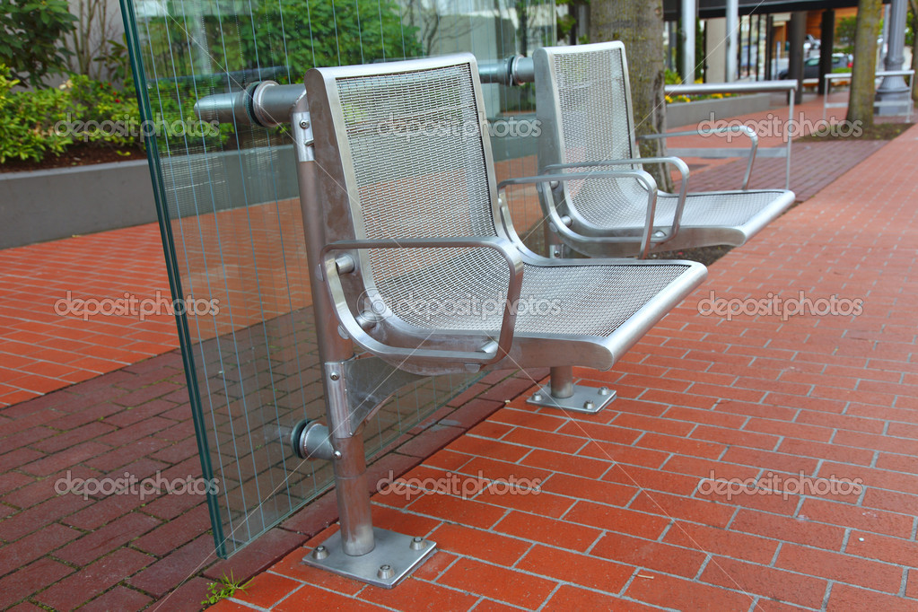 Stainless steel chairs at a bus stop.
