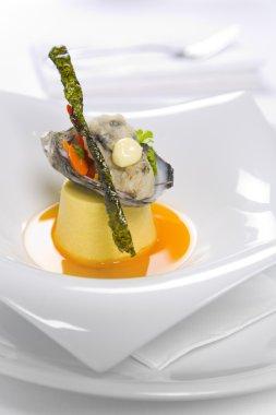 Oysters Kilpatrick served on designer plate in restaurant