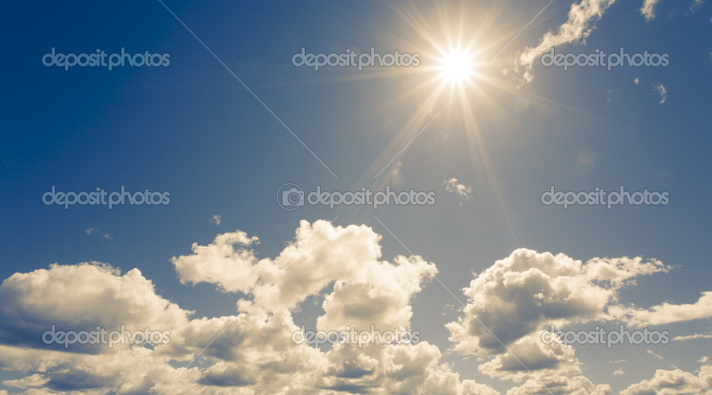 Bright sun on blue sky with fluffy clouds