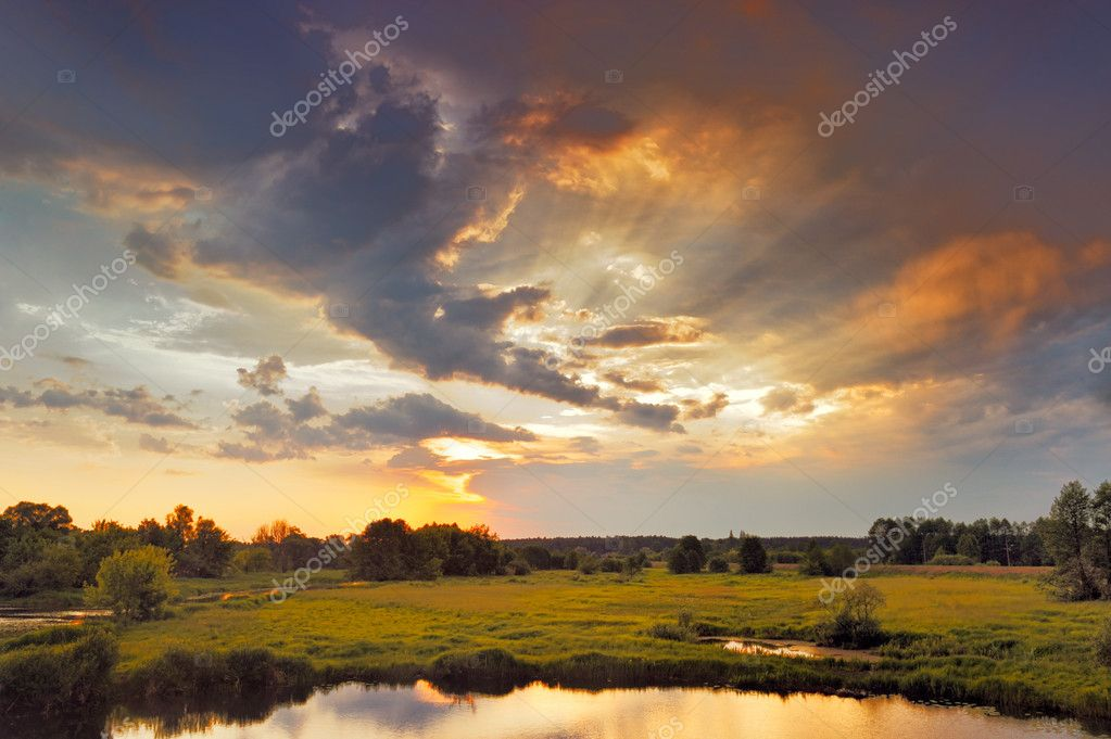 Beautiful sunrise and dramatic clouds on the sky. Flood waters of Narew riv