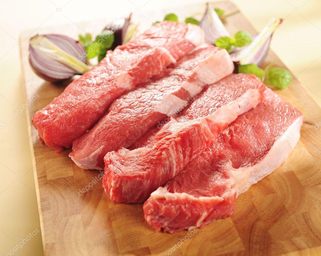 Raw beef steaks. Arrangement on a cutting board.