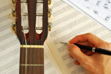 Guitar with hand composing music on manuscript