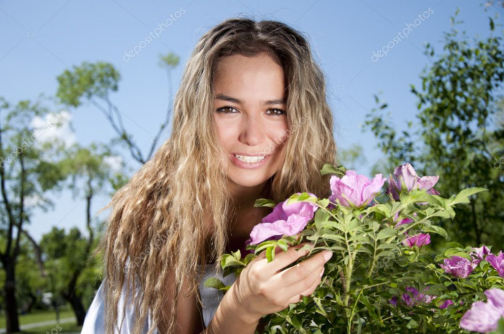 Young woman standing near a dogrose