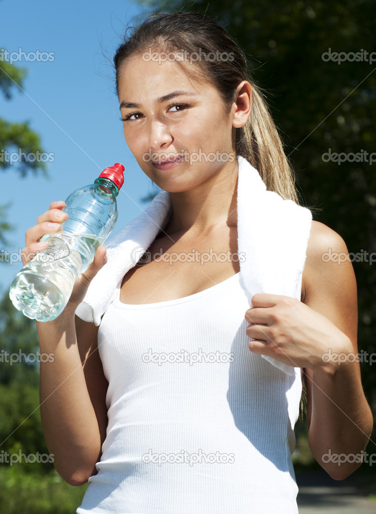 Young woman drinking water after exercise