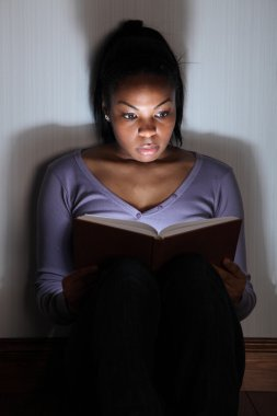 Young black woman reading scary thriller book