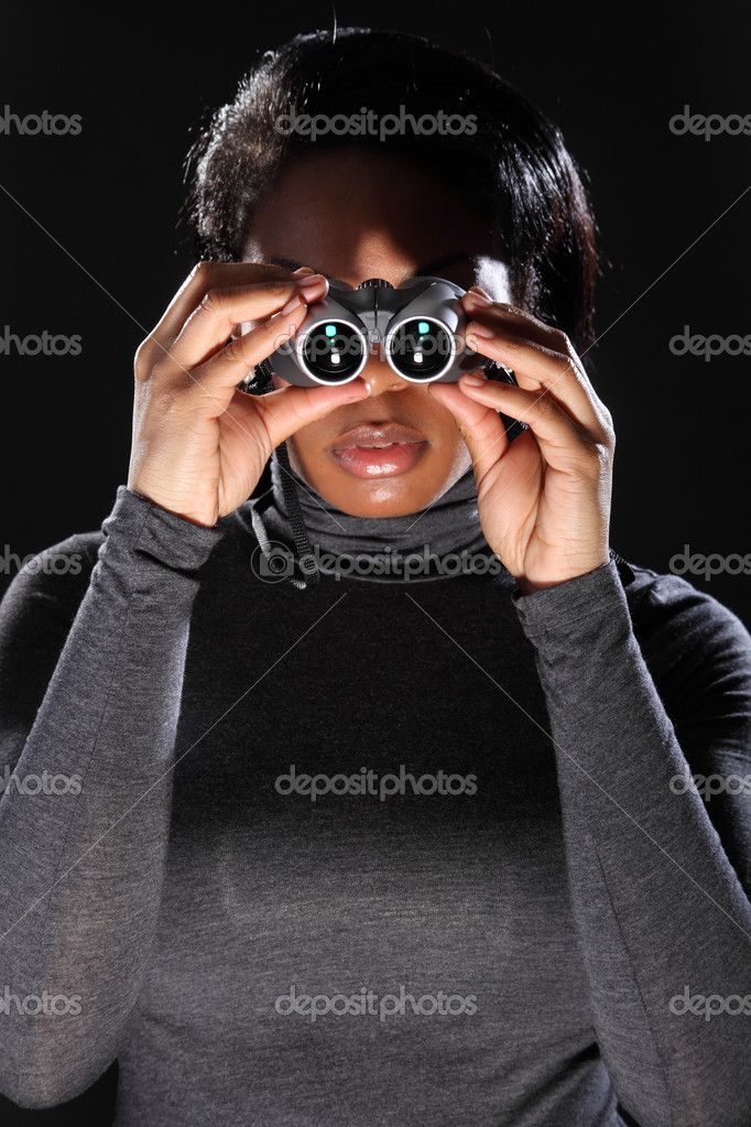 Young woman spy looking through binoculars
