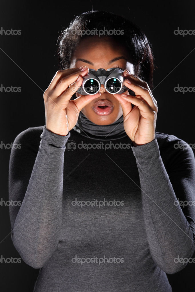 Young woman surprised while using binoculars