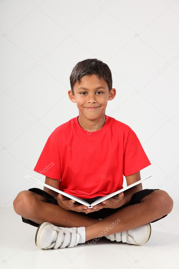 Happy smile from young boy reading book