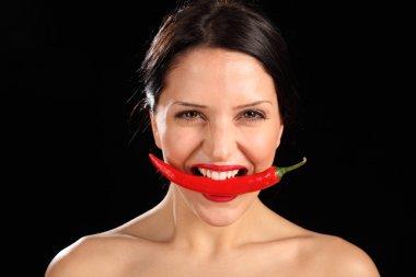 Beautiful woman biting on red chili pepper