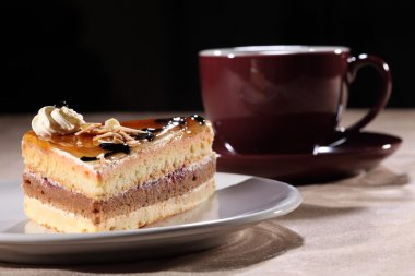 Cup coffee and cake with chocolate sauce topping