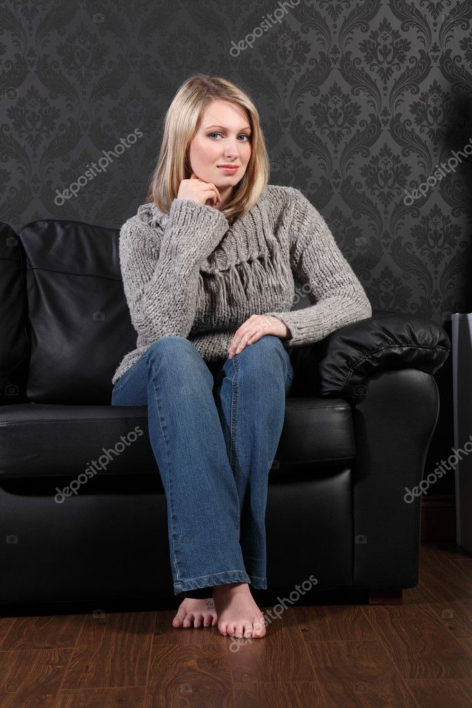 Beautiful blonde woman home sits on leather settee