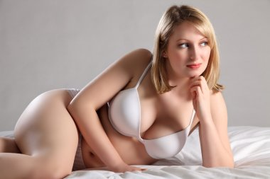 Sexy voluptuous blonde woman in white underwear
