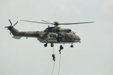 Two soldiers hanging from a helicopter