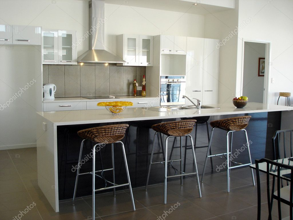 Spacious white open plan kitchen with breakfast bar  Stock Photo