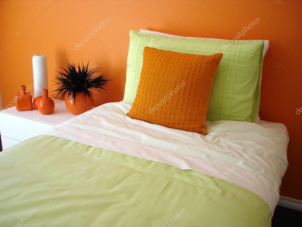 chambre orange vibrante avec linge de lit vert — Photographie scarfe ...