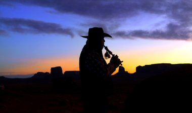 Navajo Native American Indian playing flute at sunrise