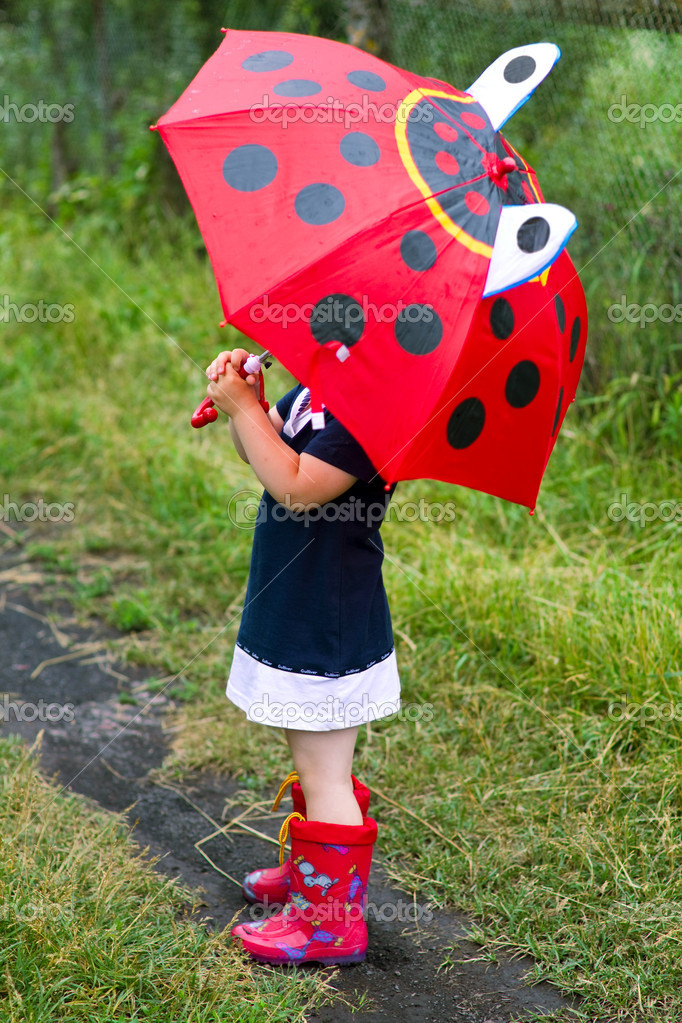 The little girl, umbrella and rubber boots