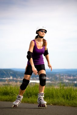 Young woman on rollerblades in the country