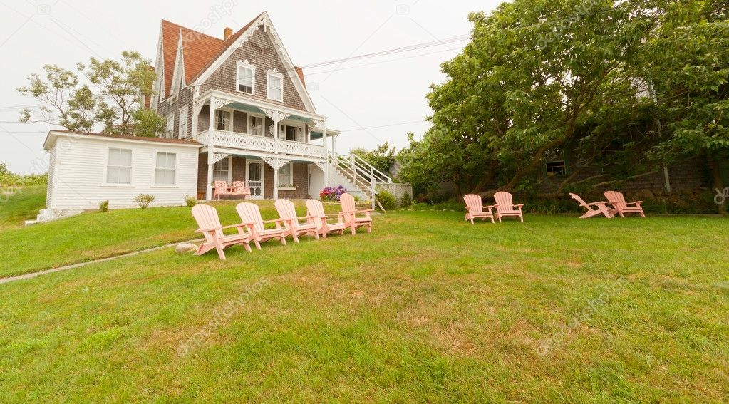 Vacation summer home with pink lawn chairs.