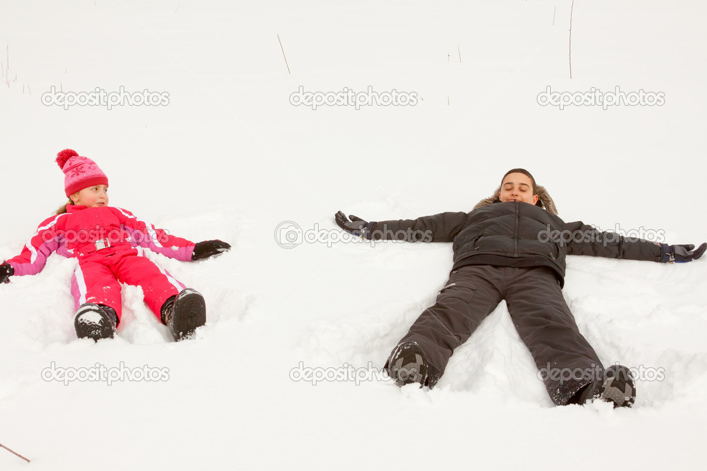 Brother and sister playing Snow Angels.