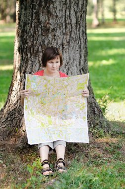 Woman with map sitting under a tree