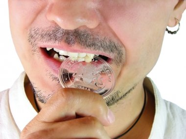 Closeup of man biting a coin to verify its authenticity on a whi
