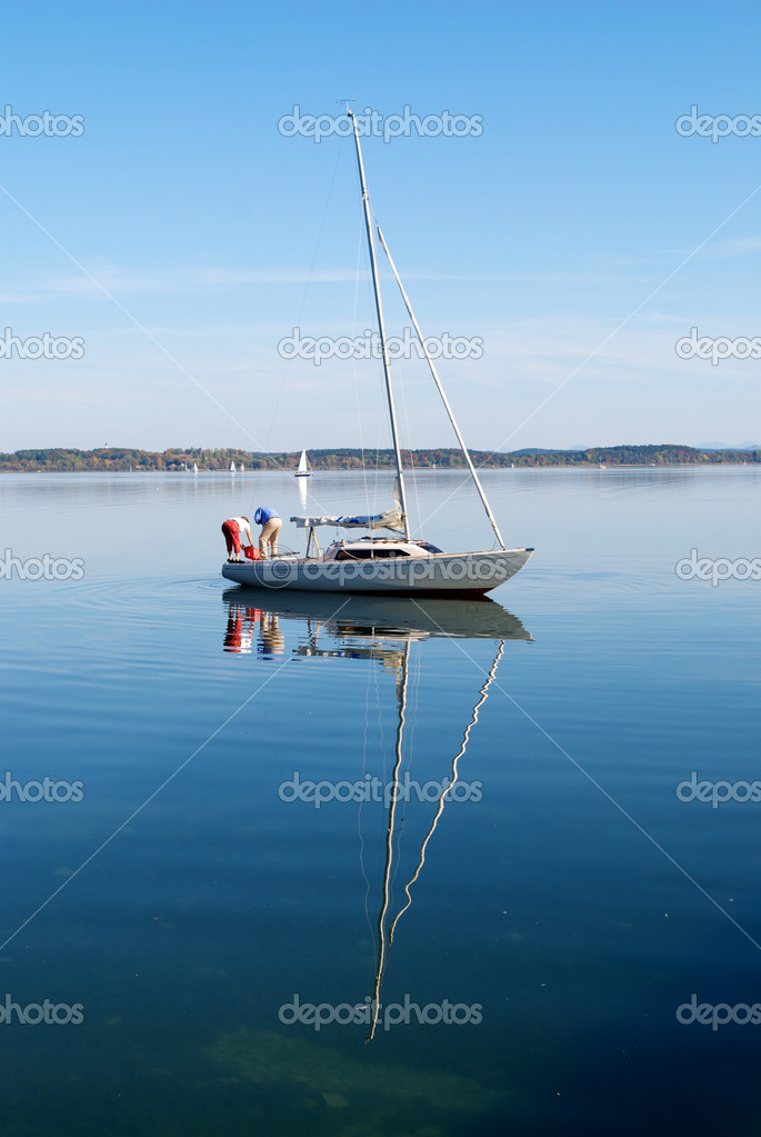 A couple prepare their sailing boat in peaceful lake