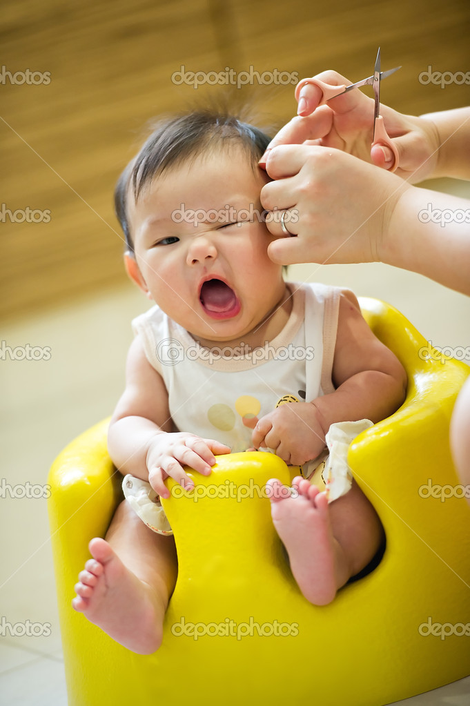 6 Month Old Asian Baby Girl Having A Haircut Stock Photo
