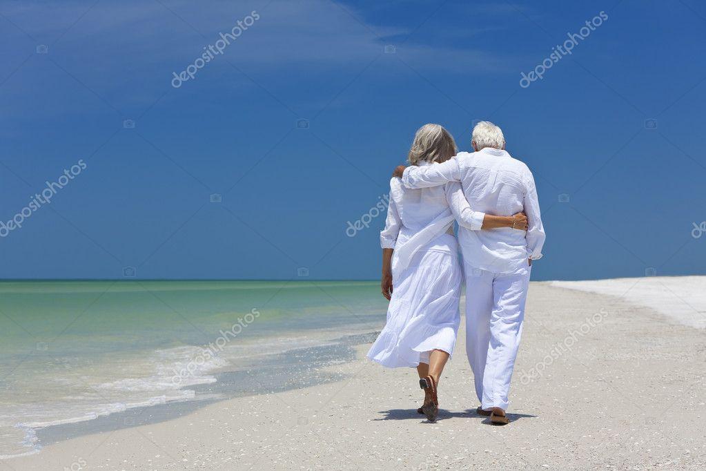 Вид сзади Пожилые супружеские пары, ходить в одиночку на тропическом пляже — Стоковое фото