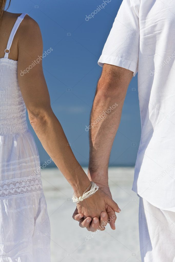 67725f15d3bd Rear view of man and woman romantic couple in white clothes holding hands  and walking on a deserted tropical beach with bright clear blue sky — Photo  by ...