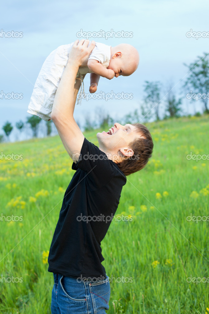 Happy young man playing his baby boy on nature on slope