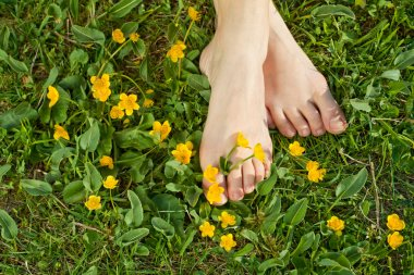 Woman resting her feet in the fresh spring vegetation