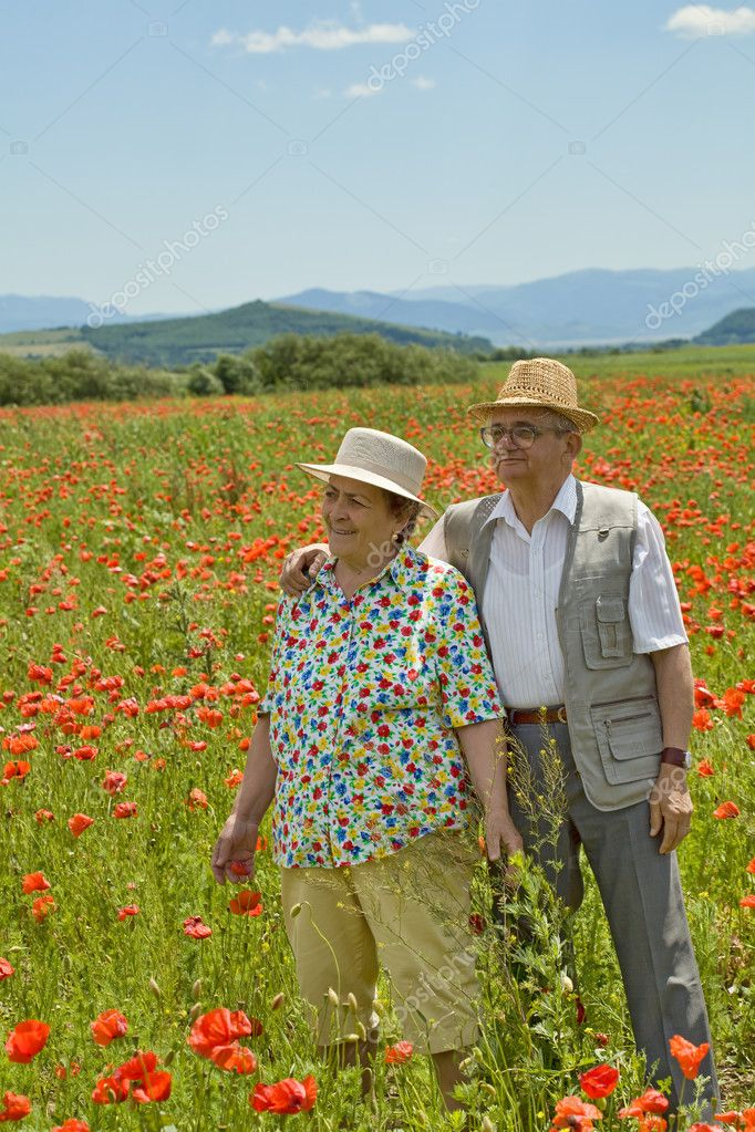 Senior couple on poppy field in early summer