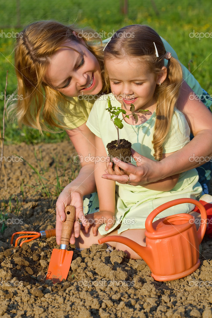 Woman and little girl growing healthy food