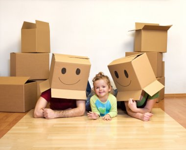 Family playing with cardboard boxes in their new home