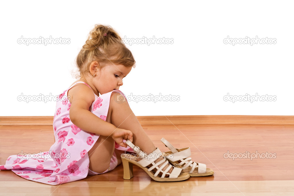 Little girl trying her mother's shoes on the floor - isolated