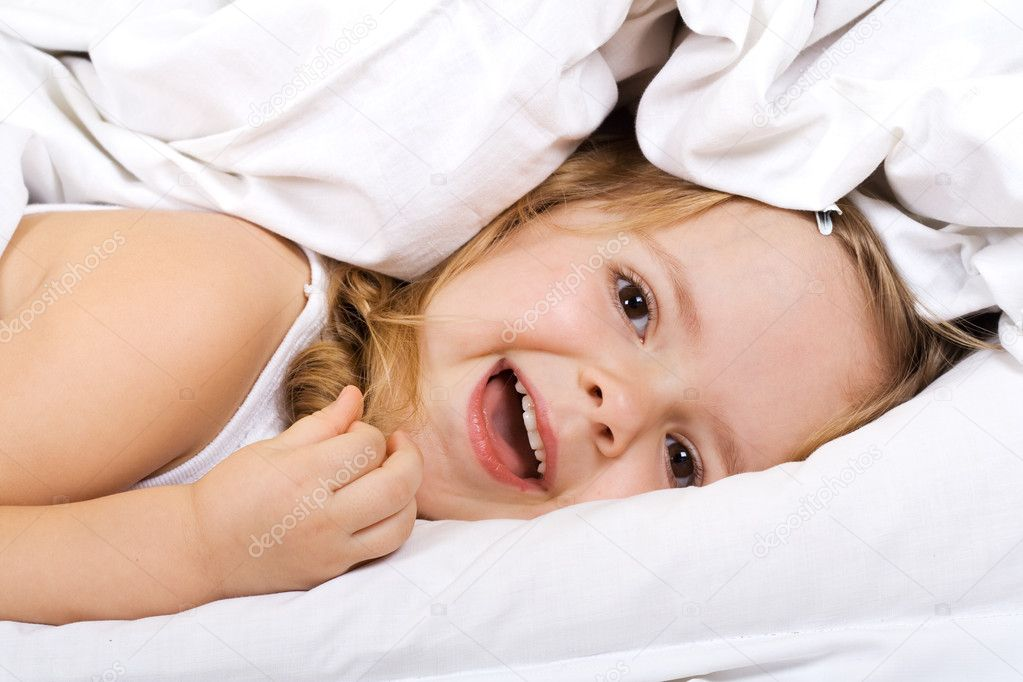 little girl laying in bed under the quilt stock photo ilona75 6409632. Black Bedroom Furniture Sets. Home Design Ideas