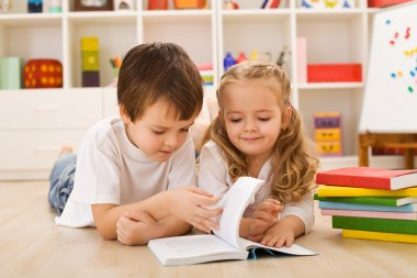 School boy teaching and showing her sister how to read