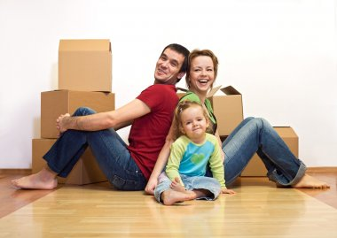 Happy family in their new home with cardboard boxes