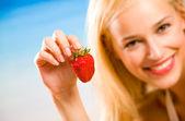 Fotografie junge schöne lächelnden blonden Frau mit Erdbeere am Meer/Strand