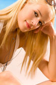 Fotografie Young beautiful blond woman in bikini with cellphone or media pl